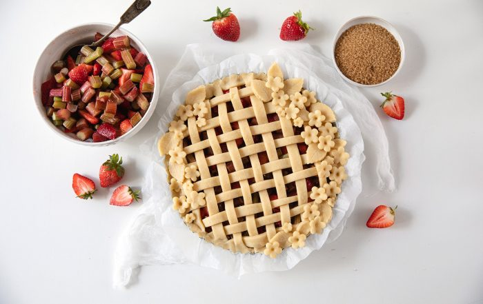 Mansikka-raparperipiirakka ja kulhollinen mansikoita pöydällä.
